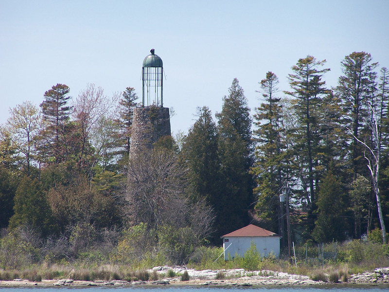 Construction of the old Baileys Harbor Light was begun in 1852. Built of native stone, the tower was topped with a birdcage-style lantern room containing a Sixth Order Fresnel lens, later upgraded to a Fifth Order lens. In 1866 its use was replaced by construction of the range lights on Baileys Harbor's west shore, and a light on Cana Island. The lights shined for the last time in 1869, and the island is now privately owned.