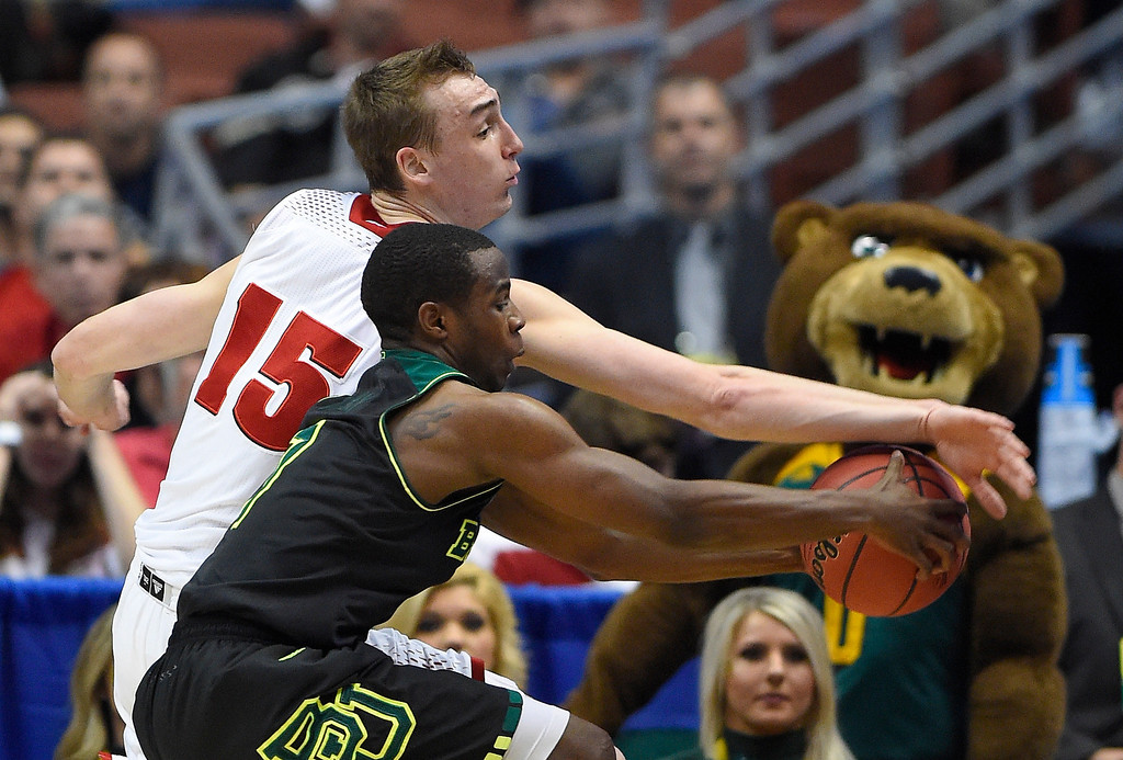 . Wisconsin forward Sam Dekker (15) and Baylor guard Kenny Chery reach the ball during the first half of an NCAA men\'s college basketball tournament regional semifinal, Thursday, March 27, 2014, in Anaheim, Calif. (AP Photo/Mark J. Terrill)