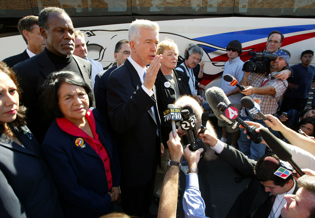 ". SAN JOSE, CA - OCTOBER 5:  California Gov. Gray Davis makes a statement to the press regarding sexual harassment allegations against candidate Arnold Schwarzenegger, with actor Danny Glover (Top L) and Dolores Huerta (Bottom L), co-founder of the United Farm Workers union, at his side as he arrives at a campaign stop at the International Brotherhood of Electrical Workers October 5, 2003 in San Jose, California. Davis is on a three-day ""Just Say No Fly Around\"" tour of the state to campaign in the final days before the October 7 special gubernatorial recall election.  (Photo by David McNew/Getty Images)"