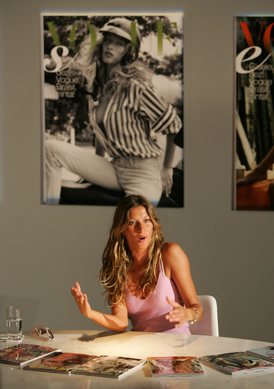 . Brazilian supermodel Gisele Bundchen gestures during an event to celebrate her 10 years of modeling with Vogue Brasil magazine during the Sao Paulo Fashion Week on Wednesday, Jan. 19, 2005. In the background, her first cover with the magazine. (AP Photo/Victor R. Caivano)