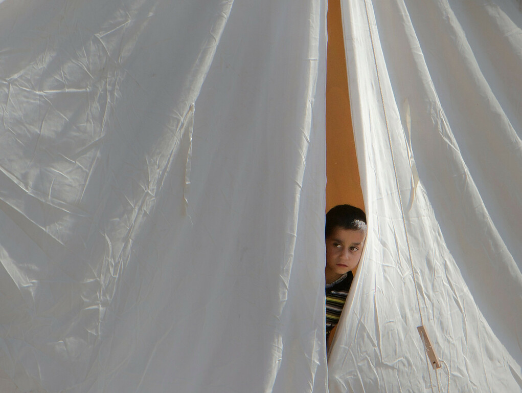 . FILE - A Syrian refugee boy peers from a tent in a camp in Boynuyogun, Turkey, Tuesday, June 14, 2011. (AP Photo/Vadim Ghirda, File)