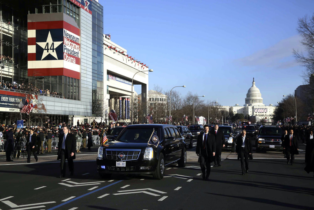 Description of . President Barack Obama and first lady Michelle Obama ride in the presidential limousine during the 57th Presidential Inauguration parade down Pennsylvania Avenue Monday, Jan. 21, 2013, in Washington. (AP Photo/Charles Dharapak)