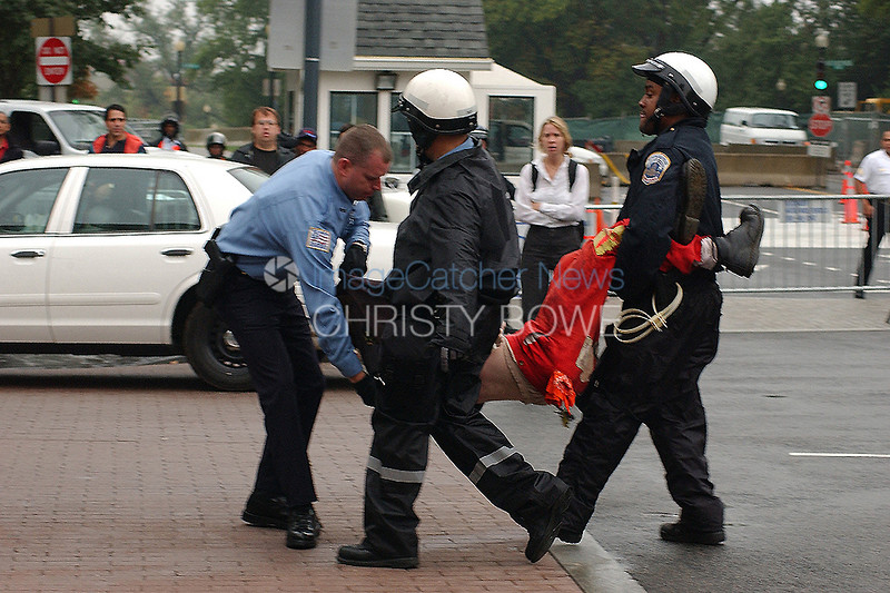 DC police drag an IMF protester from Freedom Plaza .