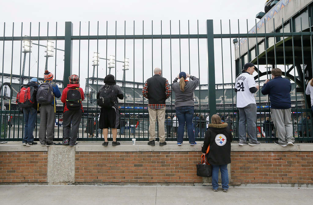 . Baseball fans look in from the outfield at Comerica Park before an opening day baseball game between the Detroit Tigers and the Minnesota Twins in Detroit, Monday, April 6, 2015. (AP Photo/Carlos Osorio)