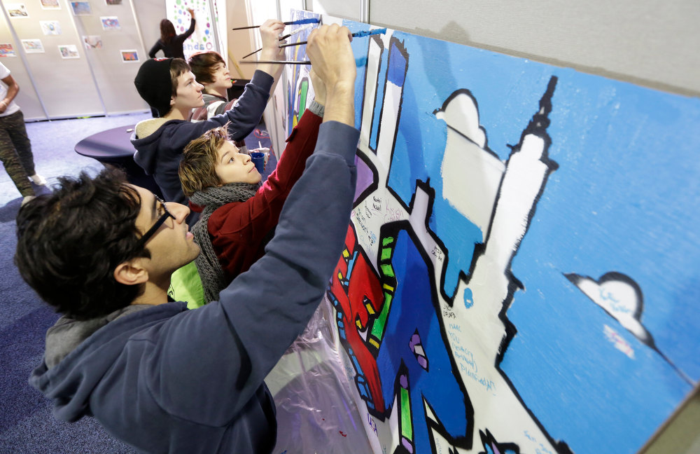 Description of . Jay Desai, of Washington, front and Ariel Timar, of Cherry Hill, N.J., center, paint a mural as they participate in the National Day of Service on the Mall as part of the 57th Presidential Inaugural festivities, Saturday, Jan. 19, 2013, in Washington, . The two were working on the Greater DC care project that will place the murals in schools and fire stations to help promote volunteerism. (AP Photo/Steve Helber)
