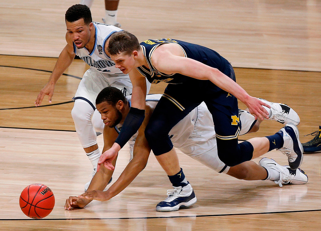 . Villanova\'s Jalen Brunson, left, Omari Spellman and Michigan\'s Moritz Wagner chase the loose ball during the first half in the championship game of the Final Four NCAA college basketball tournament, Monday, April 2, 2018, in San Antonio. (AP Photo/Brynn Anderson)