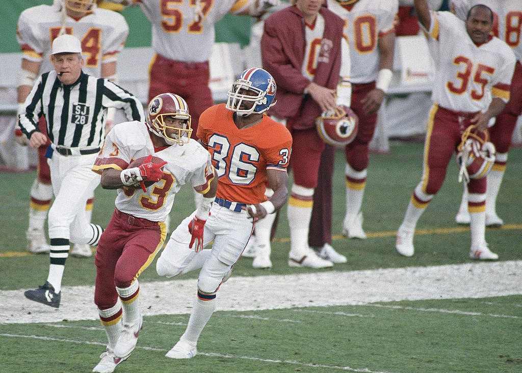 . Washington Redskins wide receiver Ricky Sanders (83) is followed by Denver Broncos cornerback mark Haynes (36) as he goes into the endzone for a touchdown in the 2nd quarter of Super Bowl XXII, Sunday, Jan. 31, 1988 in San Diego. Sanders, who set a record for most yardage in first half of a Super Bowl, scored on a pass from quarterback Doug Williams. (AP Photo/Reed Saxon)