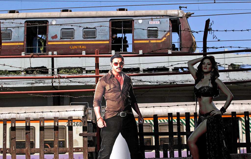 """. A train moves past cutouts of Bollywood actors John Abraham and Sunny Leone displayed outside a cinema hall in Mumbai, India, Friday, May 3, 2013. Four top Indian filmmakers have come together to make \""""Bombay Talkies,\"""" a short-film collection that hits theaters Friday to celebrate 100 years of Indian cinema. India\'s first full-length feature film \""""Raja Harishchandra,\"""" or \""""King Harishchandra,\"""" was released in 1913. Since then Indian cinema has become the largest producer of films in the world. India produced nearly 1,500 films last year, according to accounting firm KPMG. (AP Photo/Rajanish Kakade)"""