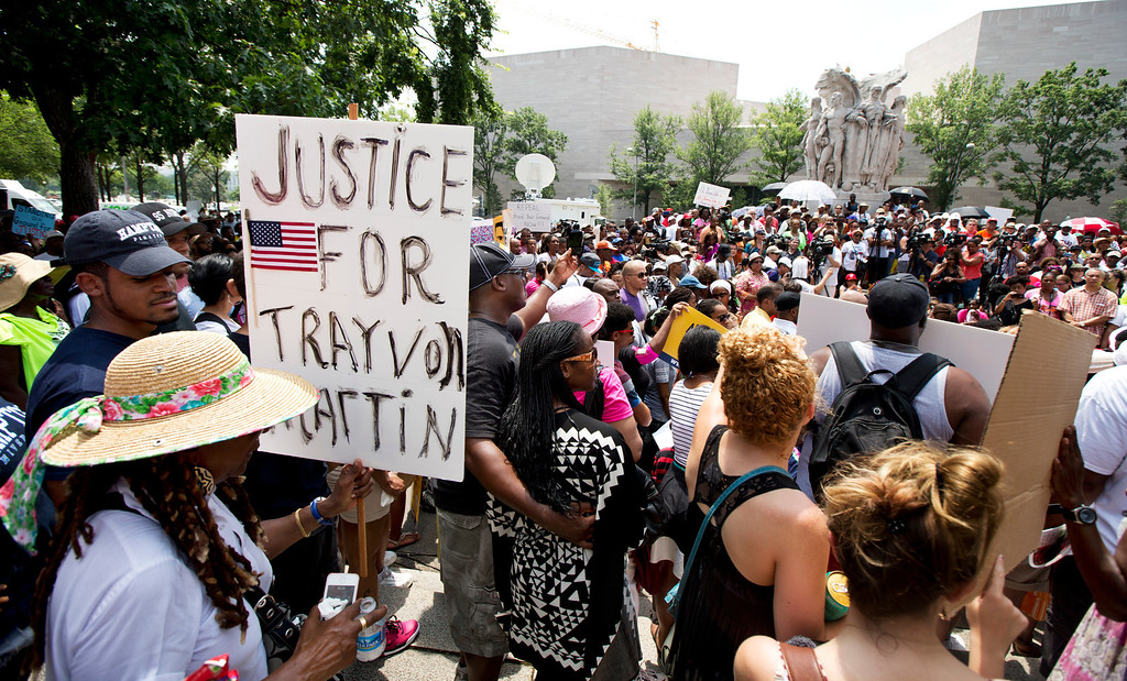 """. People gather in front of the federal court in Washington Saturday, July 20, 2013, as they demonstrate in the \""""Justice for Trayvon -100 City Vigil\"""". Friday, just before the scheduled vigils and rallies in 100 U.S. cities, President Barack Obama spoke about the raw reaction to the acquittal in a Florida court of the man who shot and killed 17-year-old Trayvon Martin. Saying \""""Trayvon Martin could have been me, 35 years ago,\"""" Obama said he had to speak because America needs to understand why so many of her citizens are in pain about Martin\'s death, and why black citizens, especially, are having a hard time looking at this as anything other than the latest manifestation of what he called \""""a history that doesn\'t go away.\"""" (AP Photo/Manuel Balce Ceneta)"""