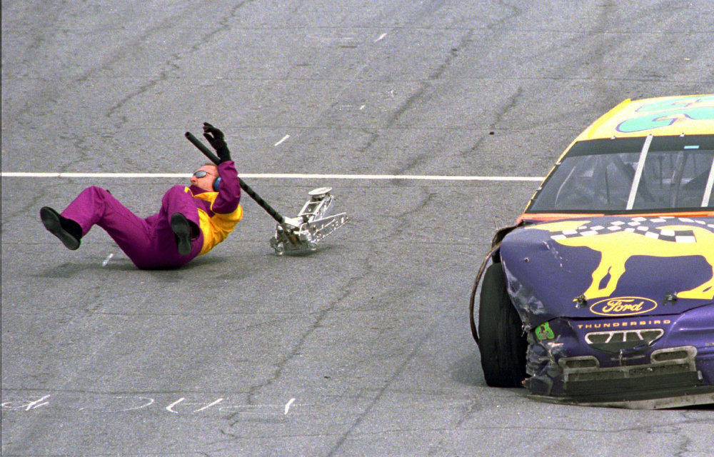 Description of . Jimmy Spencer, from Berwick, Pa., in his Ford racer, strikes his pit crew member Wayne Jenks and sends him flying after his brakes failed coming into the pits during the running of the Daytona 500 Sunday, Feb. 16, 1997, in Daytona Beach, Florida. Jenks was not seriously injured. (AP Photo/Chris O'Meara)