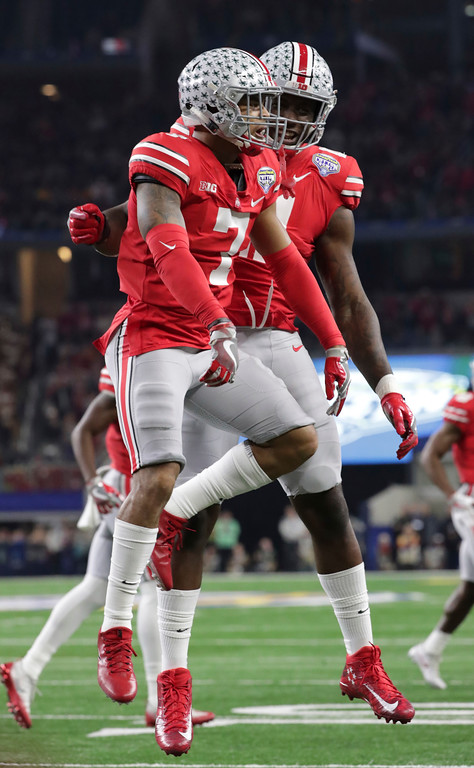 . Ohio State safety Damon Webb (7) celebrates his touchdown with teammate Jalyn Holmes (11) during the first half of the Cotton Bowl NCAA college football game against Southern California in Arlington, Texas, Friday, Dec. 29, 2017. (AP Photo/LM Otero)