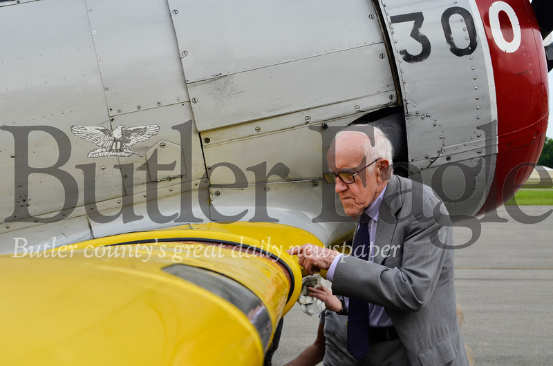 "John Zavachy, 87, examines the bugs splattered on a 1943 SNJ-4 aircraft wing after it returned from a flight. ""I didn't think there were this many bugs in the world."" Tanner Cole/Butler Eagle"