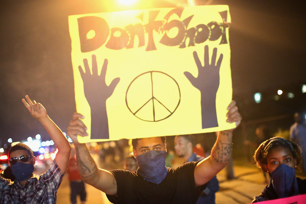. Demonstrators hold up a \'don\'t shoot\' sign during a protest at the killing of teenager Michael Brown on August 17, 2014 in Ferguson, Missouri.  Despite the Brown family\'s continued call for peaceful demonstrations, violent protests have erupted nearly every night in Ferguson since his death. (Photo by Scott Olson/Getty Images)