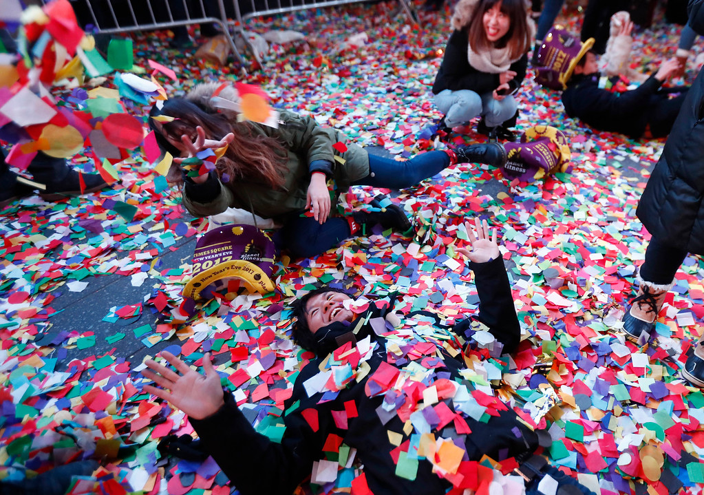 . Revelers throw confetti on themselves after after celebrating the new year in Times Square, Sunday, Jan. 1, 2017, in New York. (AP Photo/Julio Cortez)