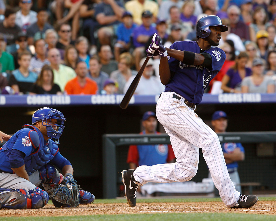 . Colorado Rockies\' Dexter Fowler, right, follows the flight of his triple to drive in two runs as Chicago Cubs catcher Wellington Castillo looks on in the fourth inning of a baseball game in Denver on Saturday, July 20, 2013, in Denver. (AP Photo/David Zalubowski)