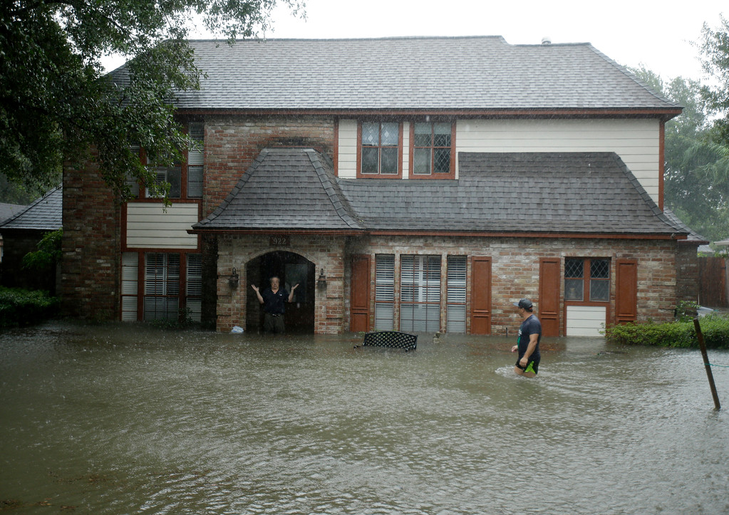 . A man standing in the doorway of his flooded home responds to an evacuation offer in a neighborhood inundated by floodwaters from Tropical Storm Harvey on Monday, Aug. 28, 2017, in Houston, Texas. (AP Photo/Charlie Riedel)