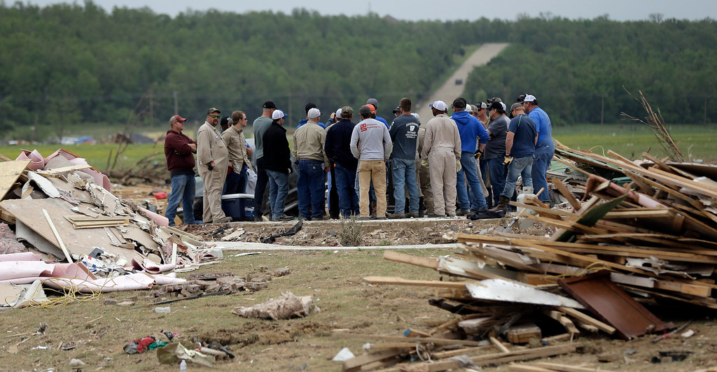 . Volunteers gather on the slab of a home destroyed by Sunday\'s tornado, Tuesday, April 29, 2014, in Vilonia, Ark. (AP Photo/Eric Gay)