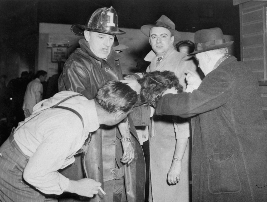. A Boston priest administers last rites of the Catholic church to a woman dragged from the fire-swept Cocoanut Grove night club in Back Bay Boston, Ma., during the night of November 28, 1942.  (AP Photo)