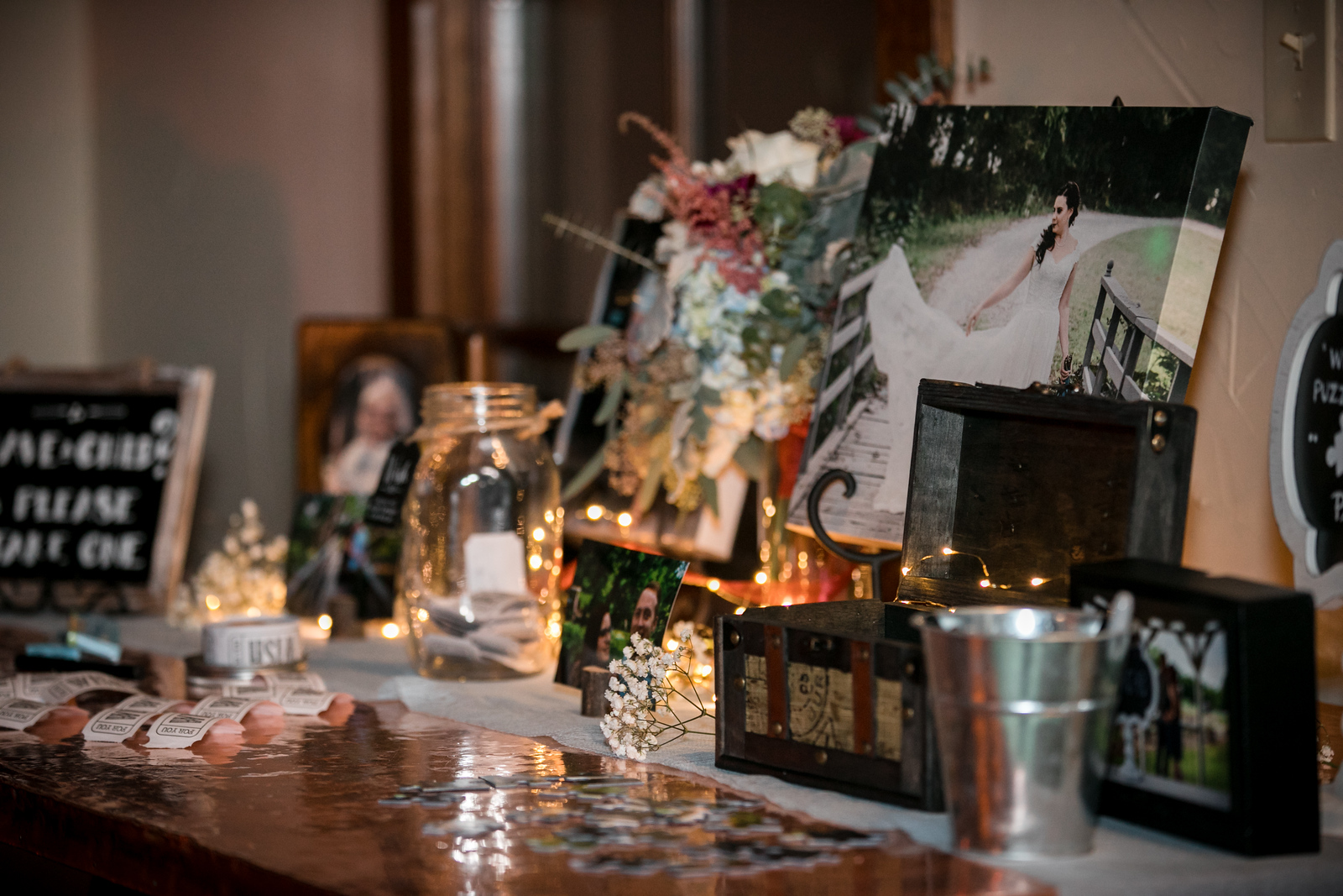 table of photos on canvas and in frames with glass jars and galvanized buckets with flowers as decoration