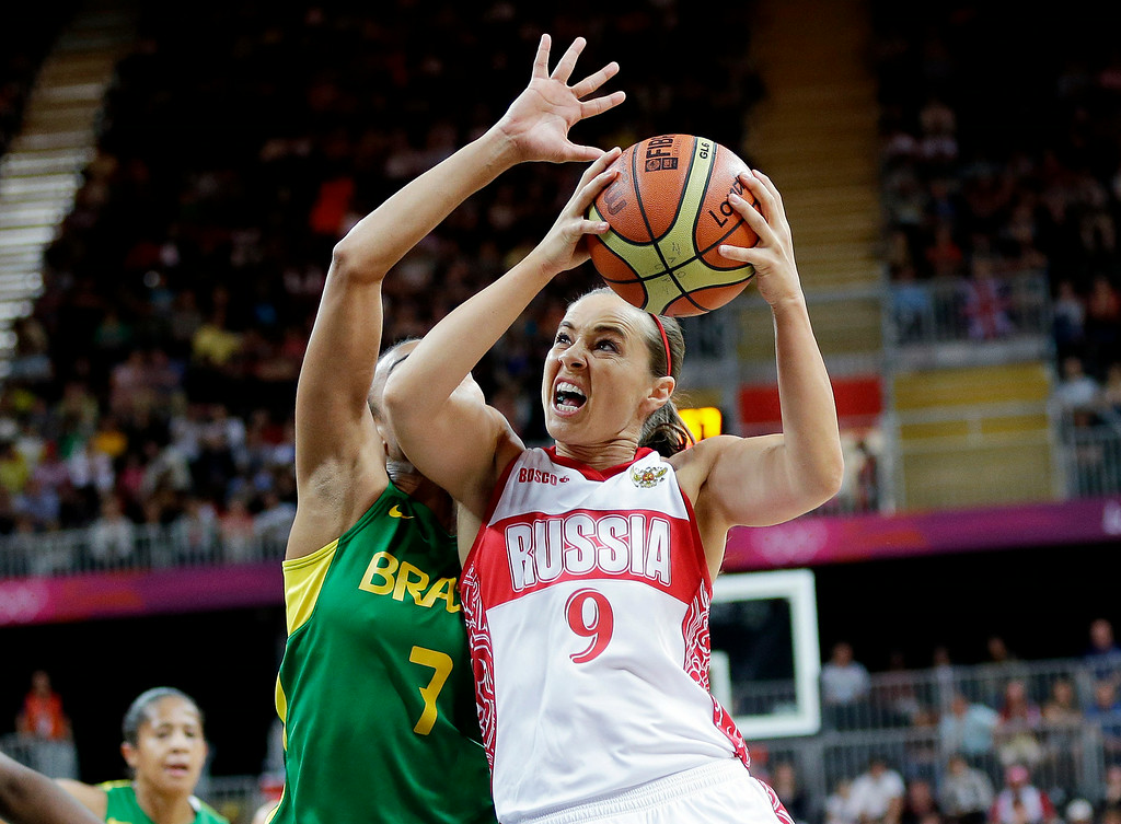 . Russia\'s Becky Hammon (9) tries to shoot as Brazil\'s Joice Rodrigues (7) defends during the second half of a preliminary women\'s basketball game at the 2012 Summer Olympics, Monday, July 30, 2012, in London. (AP Photo/Eric Gay)