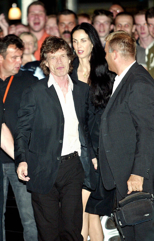 ". Rolling Stones frontman Mick Jagger celebrating 26 July 2003 in Prague his sixtieth birthday smiles to wellwishers as he and L\'Wren Scott, former model and US stylist enter a select VIP Duplex club at Wenceslas Square. The Rolling Stones were in Prague on the latest leg of their ""Forty Licks\"" world tour.     (DAVID NEFF/AFP/Getty Images)"