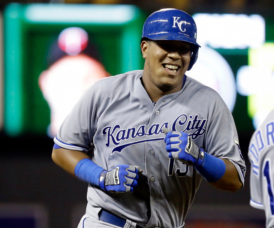 . Kansas City Royals\' Salvador Perez smiles as he passes third base coach Eddie Rodriguez following his two-run home run off Minnesota Twins pitcher Casey Fien in the eighth inning of a baseball game, Wednesday, Aug. 28, 2013 in Minneapolis. Perez went 4-for-5 with four RBIs, including another two-run home run in the fourth inning. The Royals won 8-1. (AP Photo/Jim Mone)