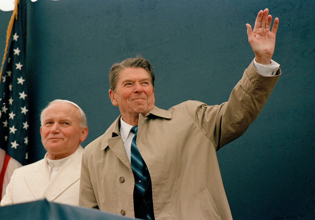 . President Ronald Reagan gestures toward the crowd as Pope John Paul II stands by his side during a joint appearance at the airport in Fairbanks, Alaska, May 2, 1984. After the meeting, Reagan flew on to Washington and the Pope to South Korea. (AP Photo/Scott Stewart)