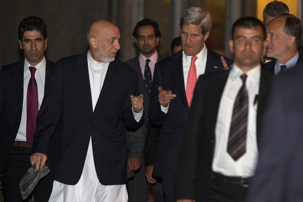 . Afghan President Hamid Karzai, second from left, walks with U.S. Secretary of State John Kerry at the Presidential Palace during Kerry\'s unannounced stop to meet wit Karzai in Kabul, Afghanistan, on Friday, Oct. 11, 2013. (AP Photo/Jacquelyn Martin, Pool)