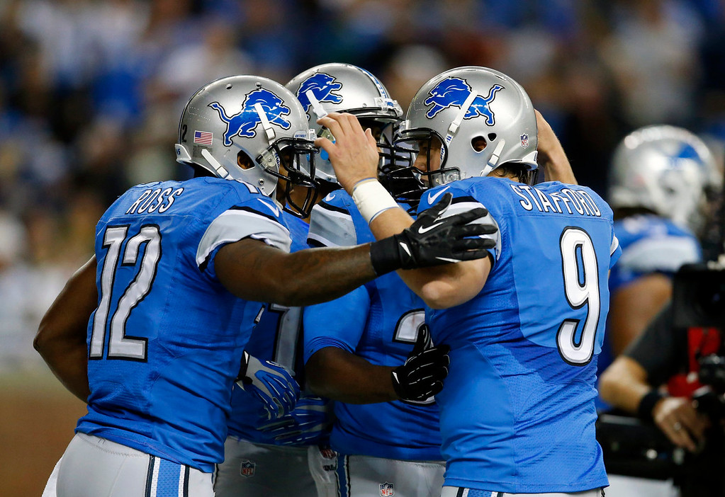 . Detroit Lions quarterback Matthew Stafford (9) congratulates wide receiver Jeremy Ross (12) after Ross\' 5-yard touchdown reception during the second quarter of an NFL football game against the Green Bay Packers at Ford Field in Detroit, Thursday, Nov. 28, 2013. (AP Photo/Rick Osentoski)