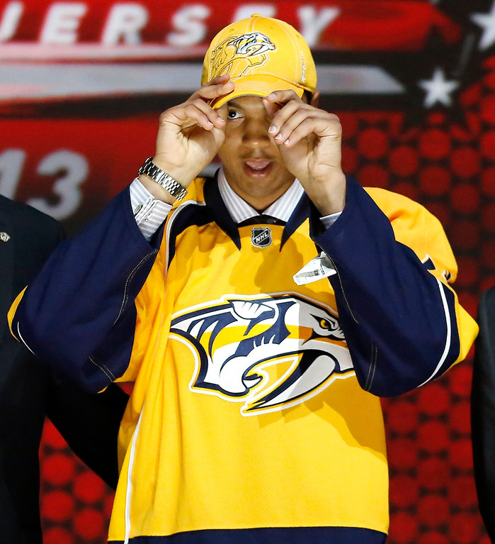 . Seth Jones tries on a Nashville Predators jersey and cap after being selected by the Predators as the fourth overall pick in the 2013 National Hockey league (NHL) draft in Newark, New Jersey, June 30, 2013. REUTERS/Brendan McDermid