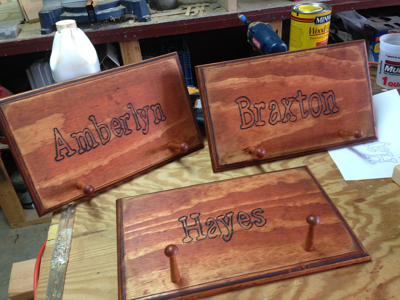 """Very simple project. Took what were basically scrap pieces of plywood (16x10 inches) and routed the edge, then drilled two 1/2"""" holes for the pegs (bought off eBay, put some wood glue on the pegs and stuck them in the hole) and then woodburned the name, and stained the whole thing. Added some simple wall hanging hardware on the back."""