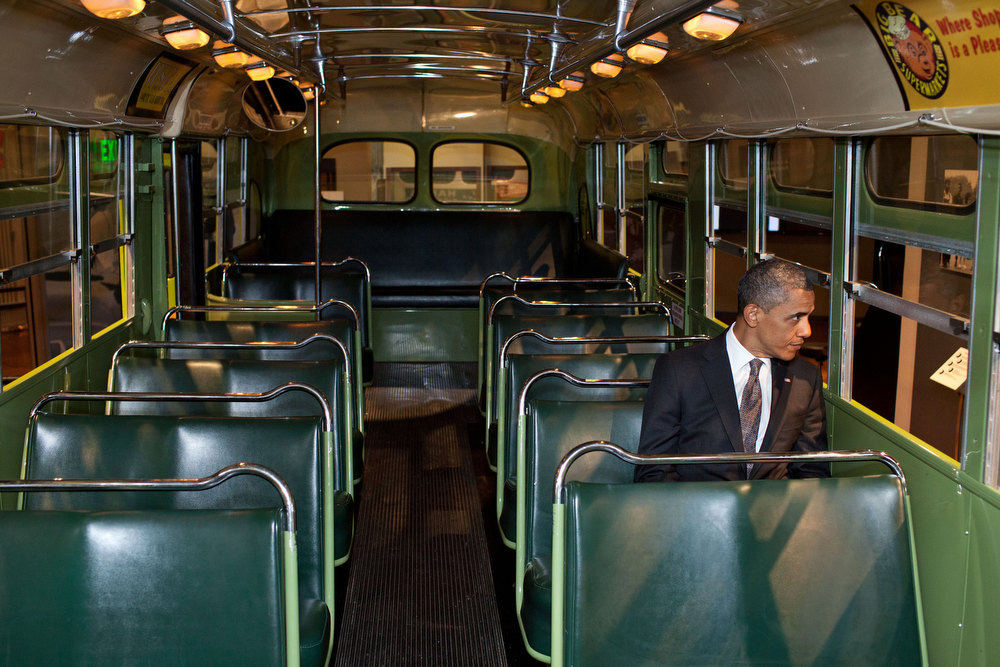 ". April 18, 2012 ""We were doing an event at the Henry Ford Museum in Dearborn, Mich. Before speaking, the President was looking at some of the automobiles and exhibits adjacent to the event, and before I knew what was happening he walked onto the famed Rosa Parks bus. He sat in one of the seats, looking out the window for only a few seconds.\"" (Official White House Photo by Pete Souza)"