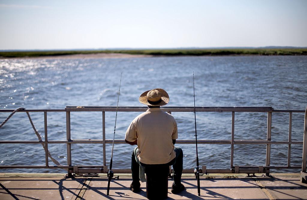 . Sapelo Island, Ga. resident, Kent Grovner, fishes off a dock on Wednesday, May 15, 2013. (AP Photo/David Goldman)