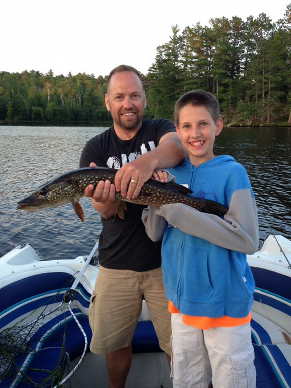 . Jaren Bispala, 45,helps Ryan Bispala,14, of Woodbury, hold Ryan\'s 29-inch northern pike he caught on Lake Vermilion July 25. (Courtesy Bispala family)