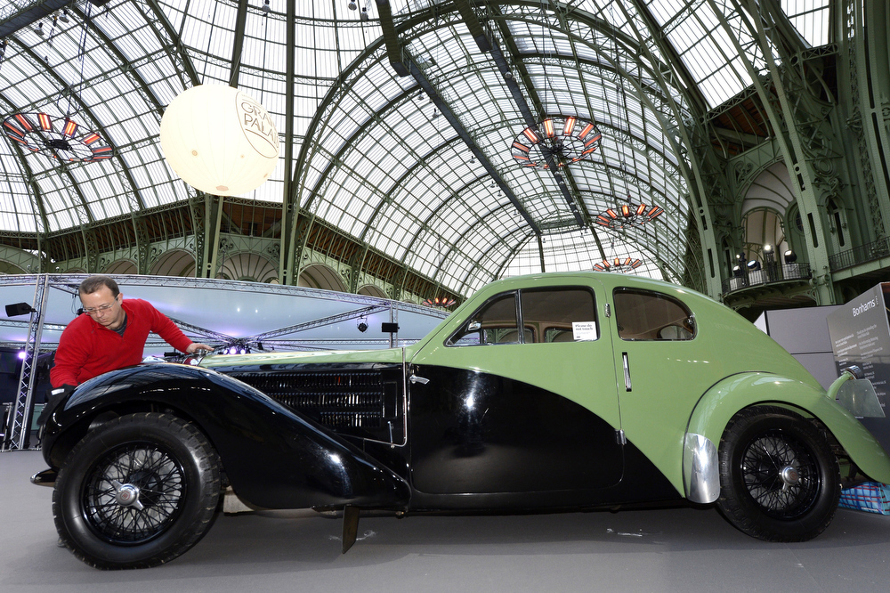 . A man cleans a Bugatti type 57C Ex (1938) as luxury vintages cars are displayed at an auction at the Grand Palais on February 6, 2013 in Paris. 125 vintage motor cars, 100 collection motorbikes and a 1920\'s Gipsy Moth plane by De Havilland, will be presented at the Bonhams auction on February 7.  BERTRAND GUAY/AFP/Getty Images