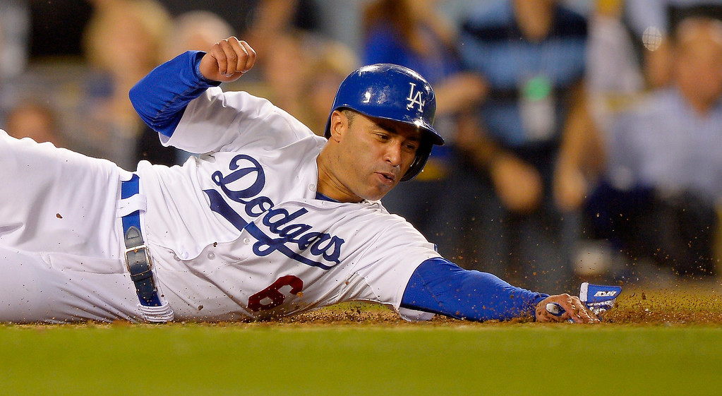 . Los Angeles Dodgers\' Jerry Hairston Jr. reaches out for the plate as he scores on a single by Mark Ellis during the fourth inning of the Dodgers\' baseball game against the Colorado Rockies, Thursday, July 11, 2013, in Los Angeles.  (AP Photo/Mark J. Terrill)