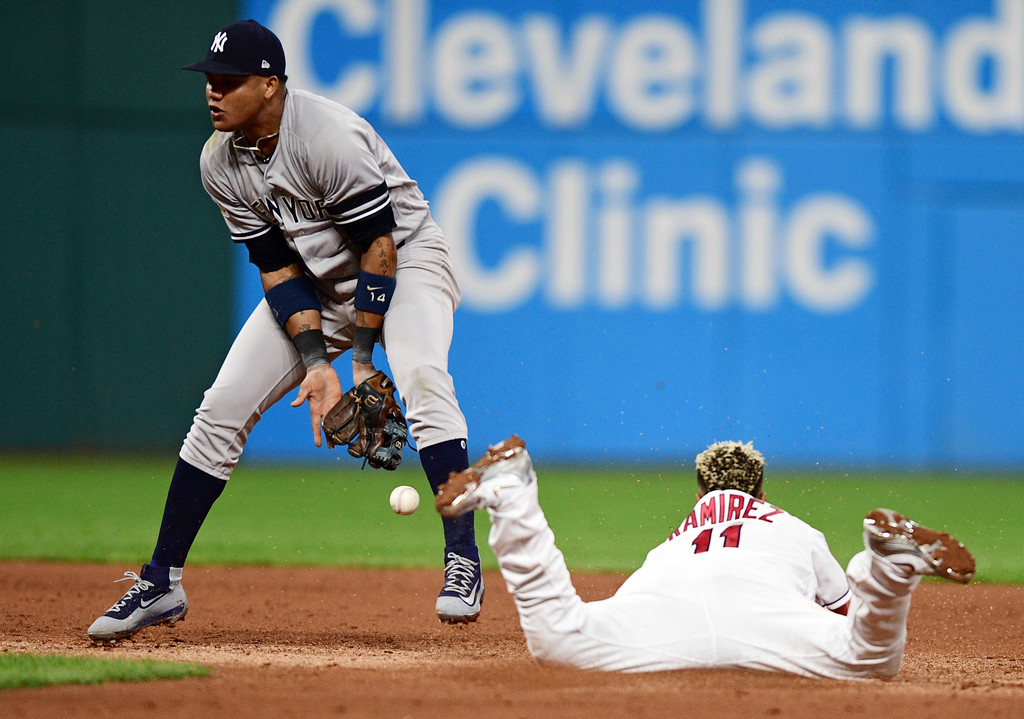 . Cleveland Indians\' Jose Ramirez, right, slides safely into second base as New York Yankees\' Starlin Castro can\'t hold on to the ball during the fifth inning of Game 1 of a baseball American League Division Series, Thursday, Oct. 5, 2017, in Cleveland. Ramirez advanced on a wild pitch by reliever Adam Warren. (AP Photo/David Dermer)
