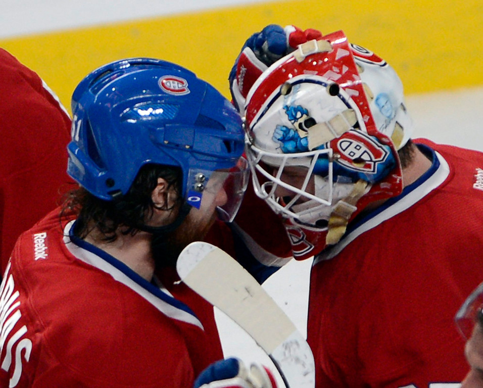 . Montreal Canadiens center David Desharnais, left, congratulates goalie Dustin Tokarski (35) after the Canadiens defeated the New York Rangers 7-4 in Game 5 of the NHL hockey Stanley Cup playoffs Eastern Conference finals, Tuesday, May 27, 2014, in Montreal. (AP Photo/The Canadian Press, Ryan Remiorz)