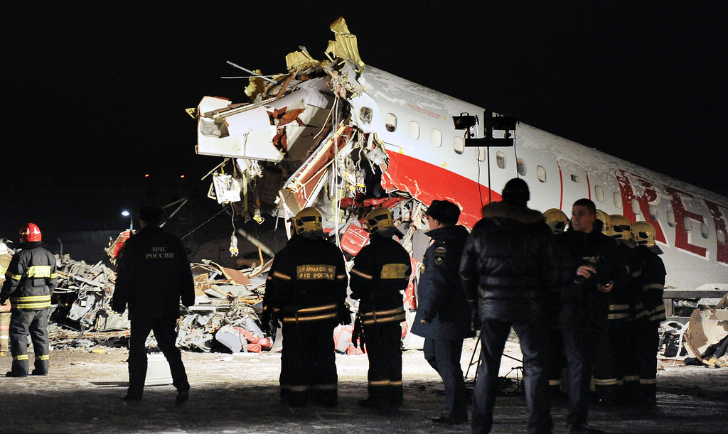 . Russian police investigators and emergency services teams work at the Tu-204 jet crash site near the Vnukovo airport outside Moscow on December 29, 2012. Four people were killed and four were injured when a Russian-made airliner overshot a runway on landing at a Moscow airport and crashed onto a nearby highway, officials said. ANDREY SMIRNOV/AFP/Getty Images
