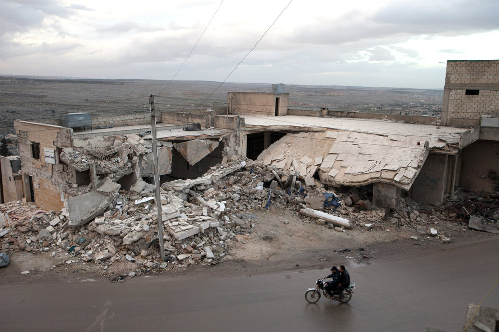 Description of . Syrians ride on their motorcycle past the remains of a building allegedly destroyed by an explosive device dropped from a Syrian jet fighter in the town of Kfar Nubul,  in the northwestern province of Idlib, on February 11, 2013.  UN Secretary General Ban Ki-moon on Monday urged the Syrian government of President Bashar al-Assad to accept an offer by the head of the opposition coalition for peace talks. DANIEL LEAL-OLIVAS/AFP/Getty Images