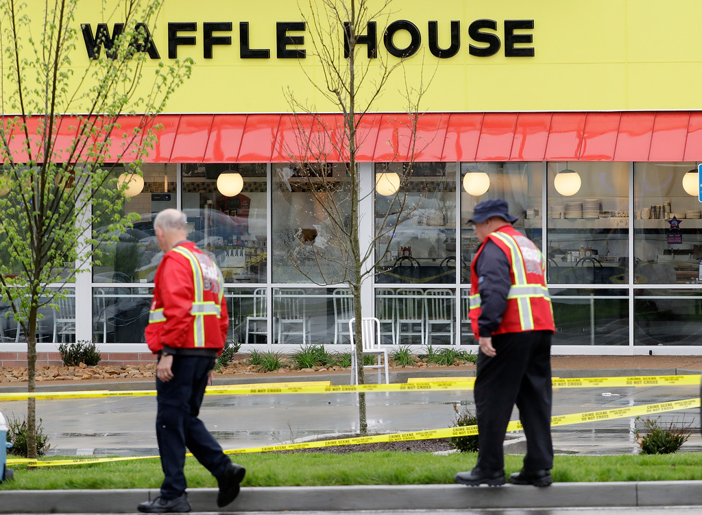 . Emergency workers walk outside a Waffle House restaurant Sunday, April 22, 2018, in Nashville, Tenn. At least four people died after a gunman opened fire at the restaurant early Sunday.(AP Photo/Mark Humphrey)