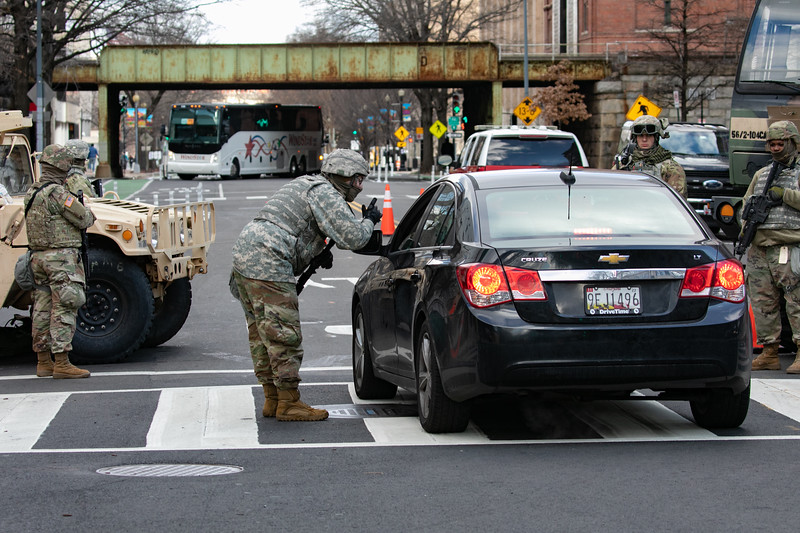 National Guard troops stop a vehicle at a checkpoint outside of the U.S. Capitol as the inauguration begins