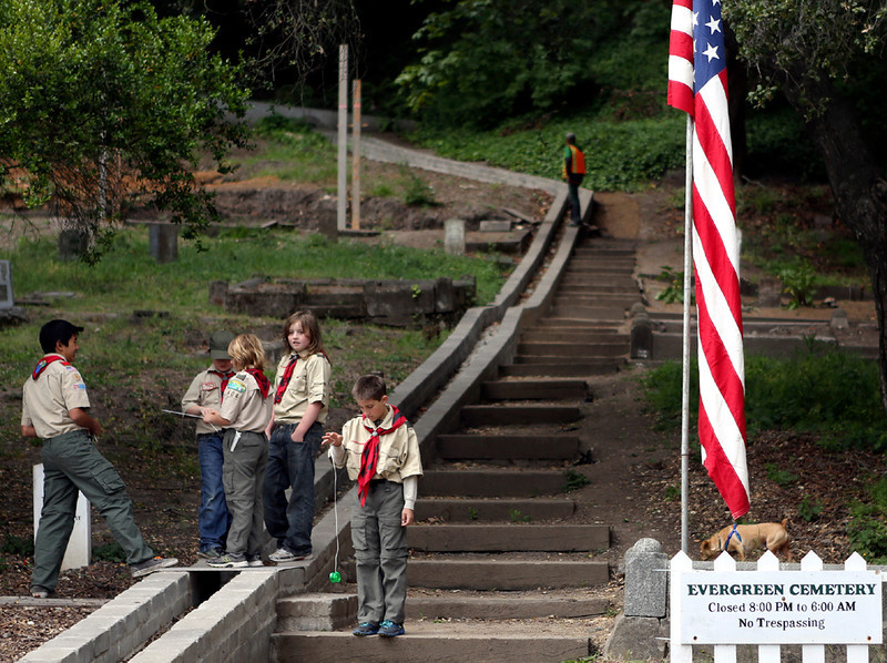 . Boy scouts take a break from setting up American flags at Evergreen Cemetery in Santa Cruz on Memorial Day Monday. (Kevin Johnson/Sentinel)