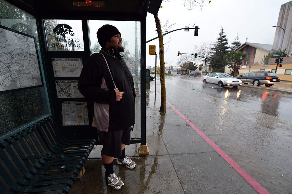 . Curtis Poppett, of Albany, stays dry as he awaits the bus on San Pablo Avenue in Berkeley, Calif., on Thursday, Dec. 11, 2014. (Kristopher Skinner/Bay Area News Group)