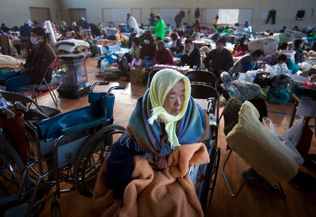 . FILE - In this Thursday, March 17, 2011, file photo, refugees, including 53 who were saved from a retirement home during the tsunami, take shelter inside a school gym in the leveled city of Kesennuma, northeastern Japan. Japan marks four years since the earthquake, tsunami, and nuclear disaster on Wednesday, March 11. (AP Photo/David Guttenfelder)