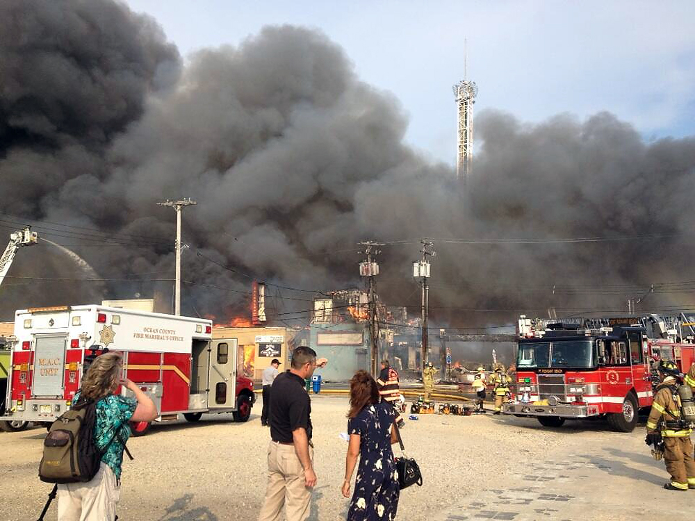 Description of . Firefighters battle a raging fire on the boardwalk in Seaside Heights, N.J. that apparently started in an ice cream shop and has spread several blocks down, Thursday, Sept. 12, 2013. The boardwalk was damaged in Superstorm Sandy and was being repaired. (AP Photo/The Asbury Park Press, Erik Larsen)