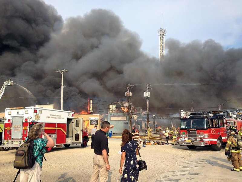 . Firefighters battle a raging fire on the boardwalk in Seaside Heights, N.J. that apparently started in an ice cream shop and has spread several blocks down, Thursday, Sept. 12, 2013. The boardwalk was damaged in Superstorm Sandy and was being repaired. (AP Photo/The Asbury Park Press, Erik Larsen)