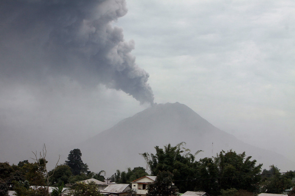 . A giant column of ash clouds rise from the crater of the Mount Sinabung volcano during a fresh eruption on September 17, 2013, as seen from Karo district. Thousands of villagers fled after Mount Sinabung\'s series of volcanic eruptions on Indonesia\'s Sumatra island, spewing rocks and red-hot ash onto surrounding villages, officials said.    KHARISMA TARIGAN/AFP/Getty Images