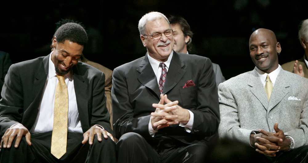 Description of . Former Chicago Bulls star Scottie Pippen, left,  shares a laugh with former coach Phil Jackson, center, and teammate Michael Jordan as Pippen's number is retired during halftime of the Bulls game against the Los Angeles Lakers on Friday, Dec. 9, 2005, in Chicago. (AP Photo/Jeff Roberson)