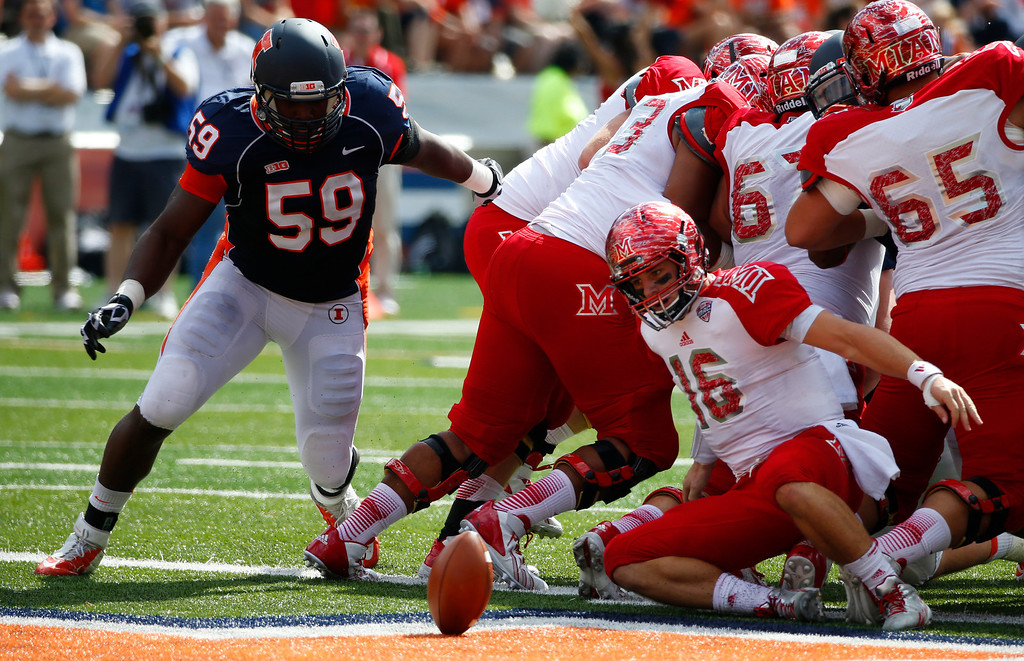 . Miami (Ohio) quarterback Austin Boucher (16) fumbles the snap as Illinois defensive lineman Tim Kynard (59) looks to recover the ball during the first half of an NCAA college football game on Saturday, Sept. 28, 2013, at Memorial Stadium in Champaign, Ill. Miami (Ohio) recovered the ball. (AP Photo/Jeff Haynes)